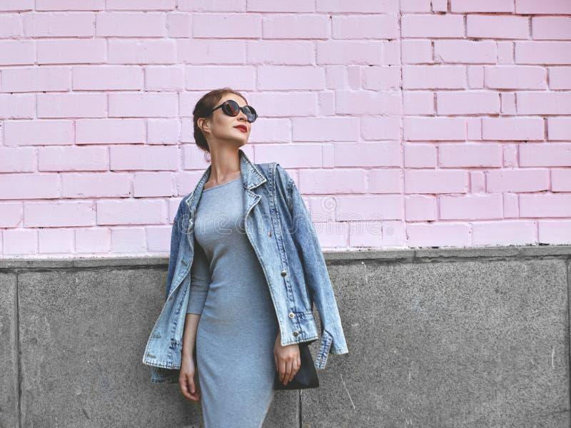 Женщина всхода стиля улицы на розовой стене Куртка джинсов девушки Swag нося, серое платье, Sunglass Образ жизни моды на открытом стоковая фотография