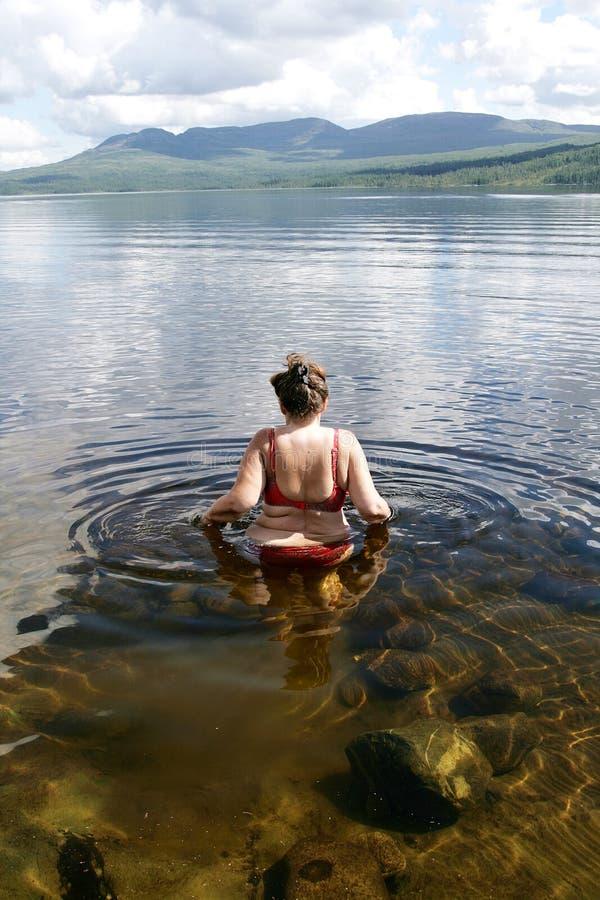 Женщина входя в озеро стоковые изображения rf