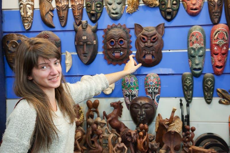 Женщина выбирает африканскую маску стоковая фотография