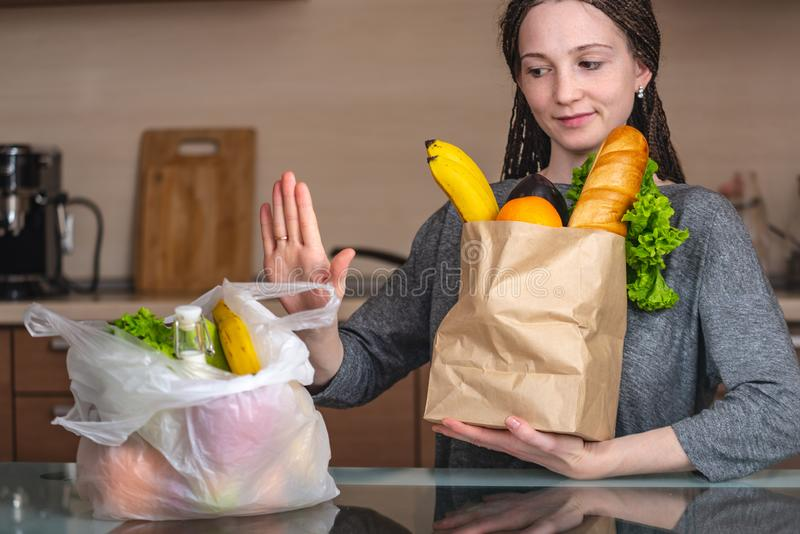 Женщина выбирает бумажный мешок с едой и отказывает использовать плас стоковые фото