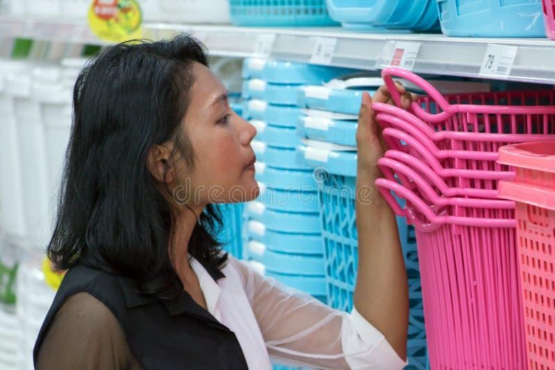 Женщина выбирает корзину одежд на моле стоковые фотографии rf