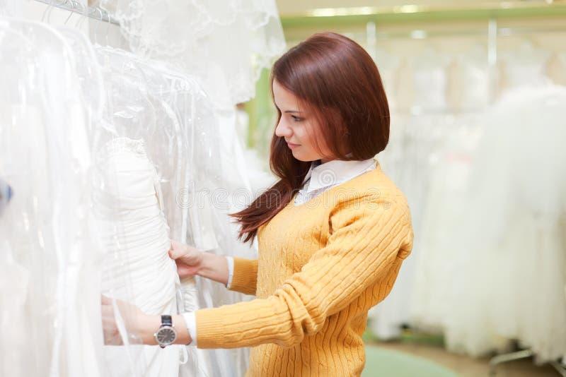 Женщина выбирая белое платье на магазине стоковое фото rf