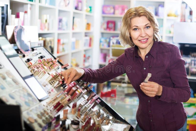 Женщина выбирая губную помаду в магазине стоковое фото