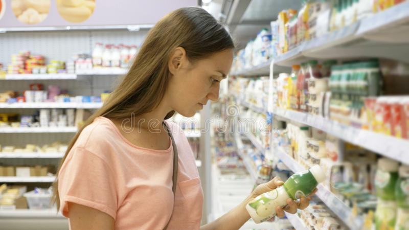 Женщина выбирая молочные продучты в холодильнике на отделе бакалеи торгового центра стоковое фото rf