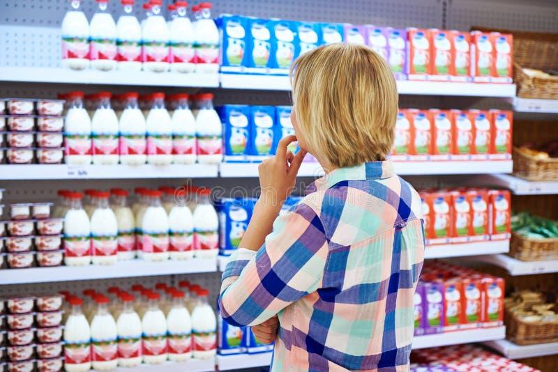 Женщина выбирая молочные продучты стоковая фотография