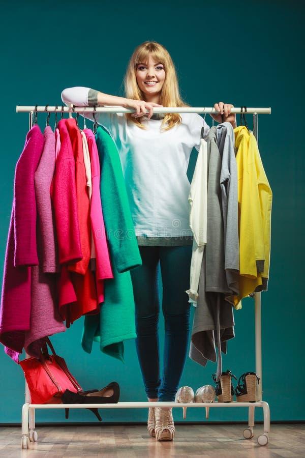 Женщина выбирая одежды для того чтобы нести в моле или шкафе стоковое изображение