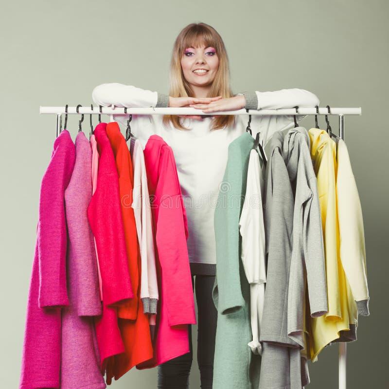 Женщина выбирая одежды для того чтобы нести в моле или шкафе стоковое фото