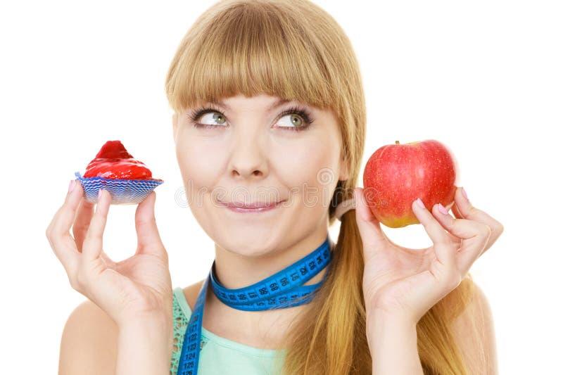 Женщина выбирая плодоовощ или торт делают диетический выбор стоковое изображение rf