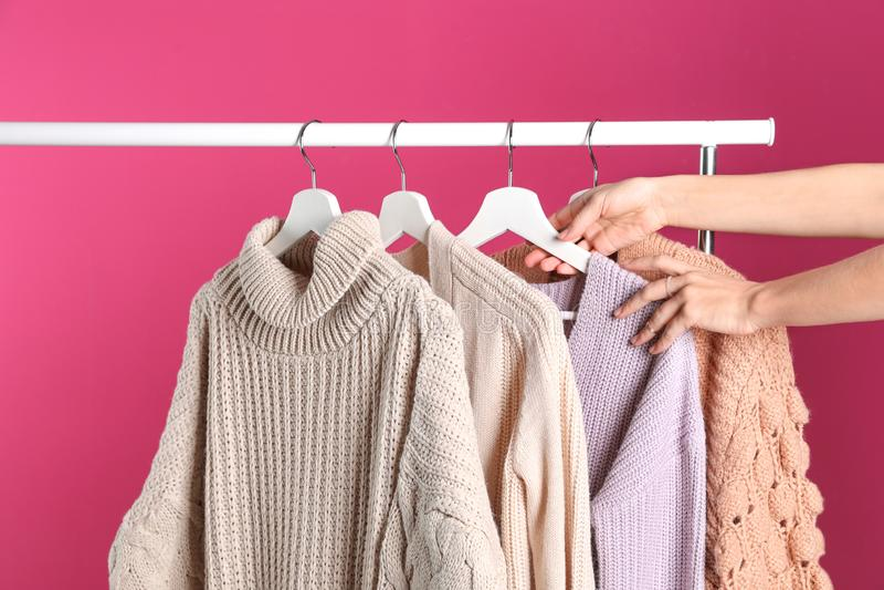 Женщина выбирая свитер на шкафе стоковые изображения