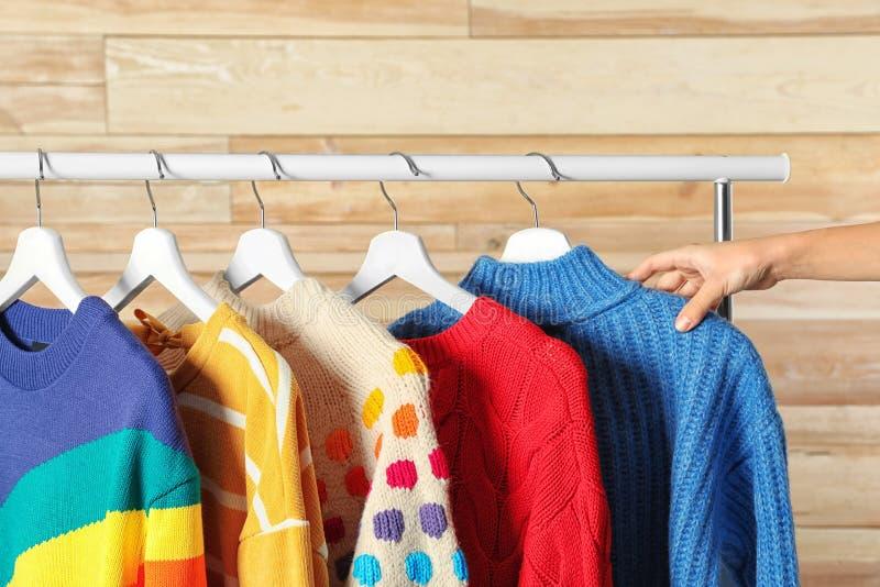 Женщина выбирая свитер на шкафе стоковые фотографии rf