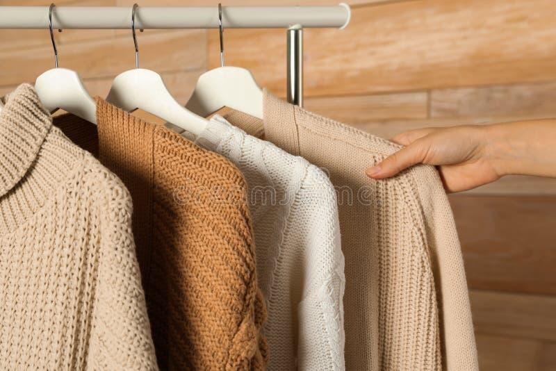 Женщина выбирая свитер на шкафе стоковая фотография rf