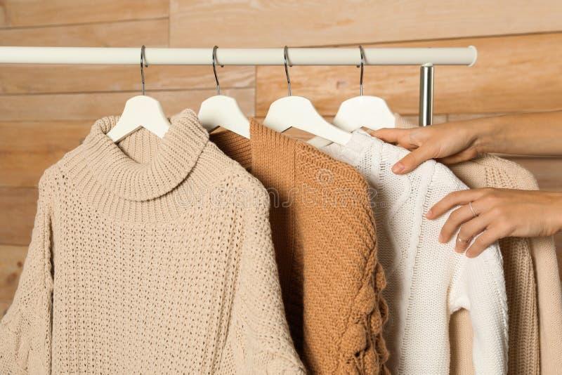 Женщина выбирая свитер на шкафе стоковое фото rf