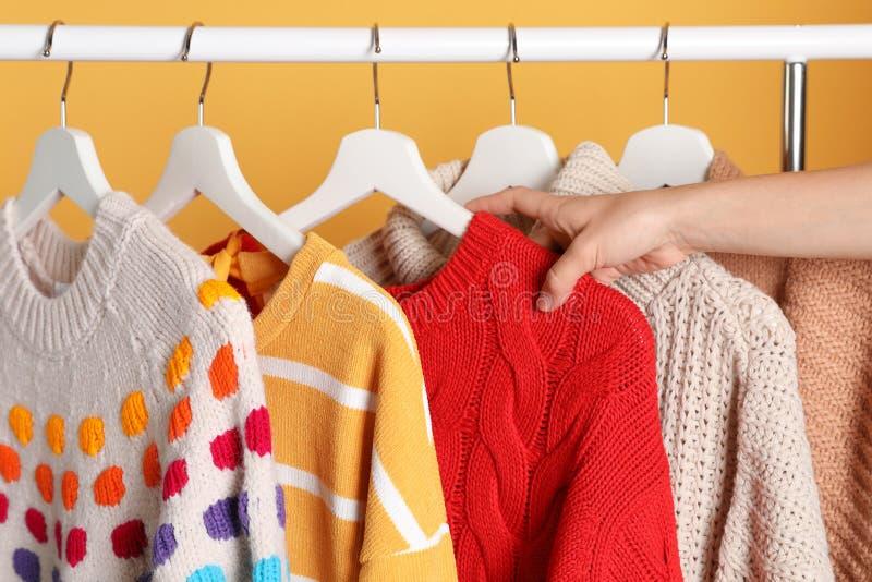 Женщина выбирая свитер на шкафе стоковое изображение rf