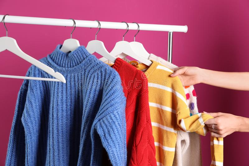 Женщина выбирая свитер на шкафе стоковые фото