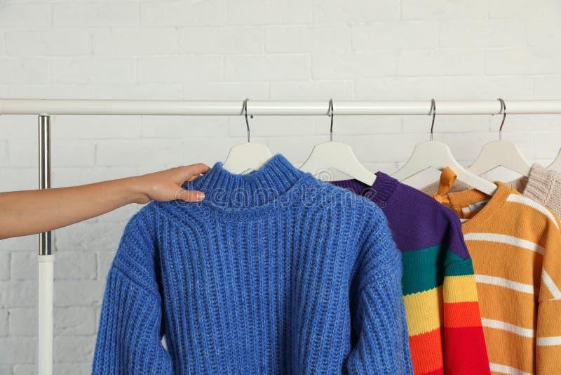 Женщина выбирая свитер на шкафе стоковое изображение