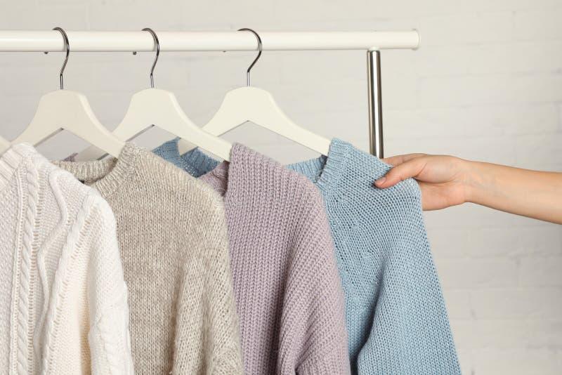 Женщина выбирая свитер на шкафе стоковое фото