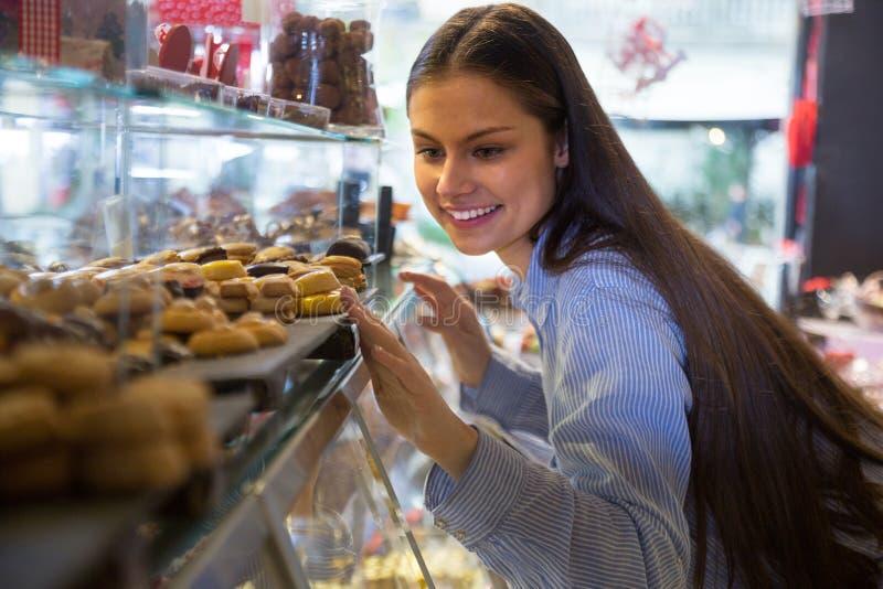 Женщина выбирая шоколады стоковые изображения