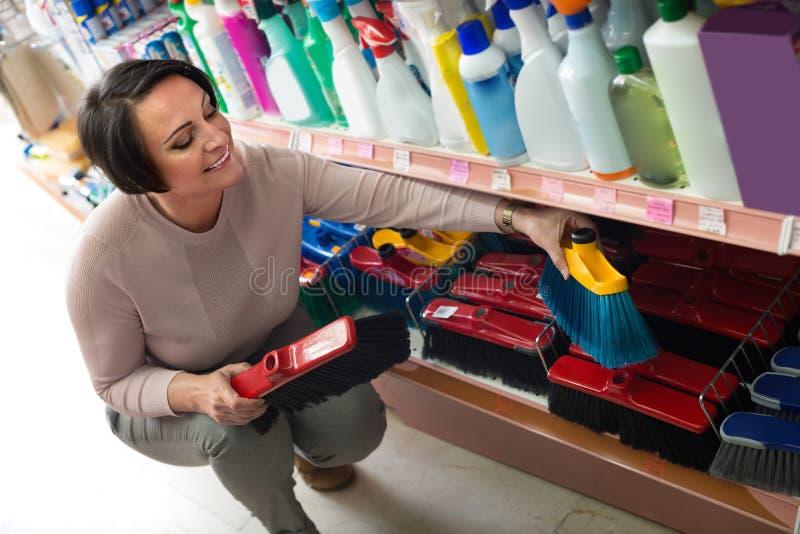 Женщина выбирая щетку чистки в магазине стоковое фото rf