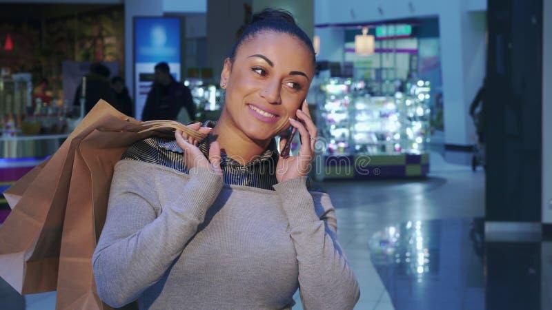 Женщина вызывает на телефоне на покупках стоковые изображения rf