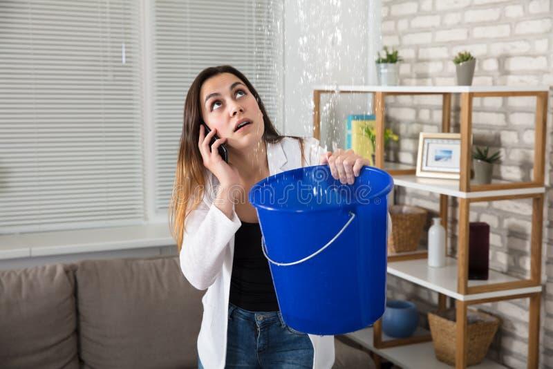 Женщина вызывая водопроводчика для утечки воды дома стоковые фото