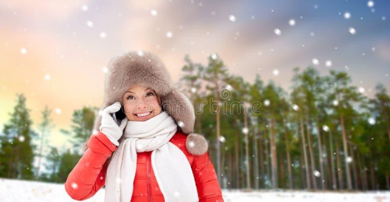 Женщина вызывая на смартфоне над лесом зимы стоковые изображения rf