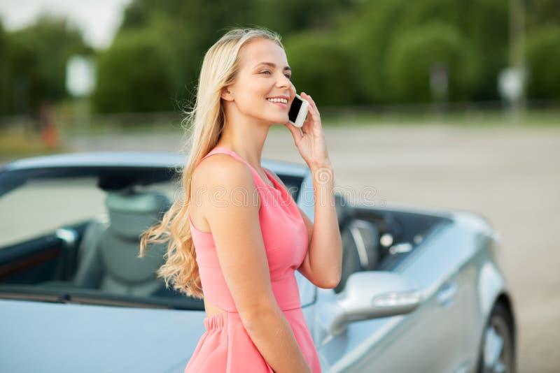 Женщина вызывая на smartphone на обратимом автомобиле стоковая фотография rf