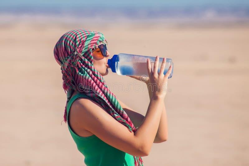 Женщина выпивает воду в пустыне Египта Концепция жаркой погоды стоковое фото rf
