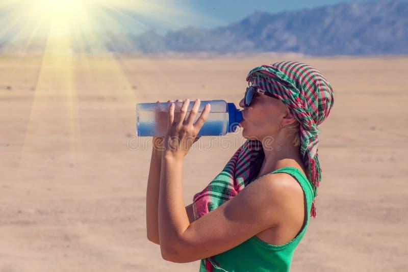 Женщина выпивает воду в пустыне Египта Концепция жаркой погоды стоковые фотографии rf