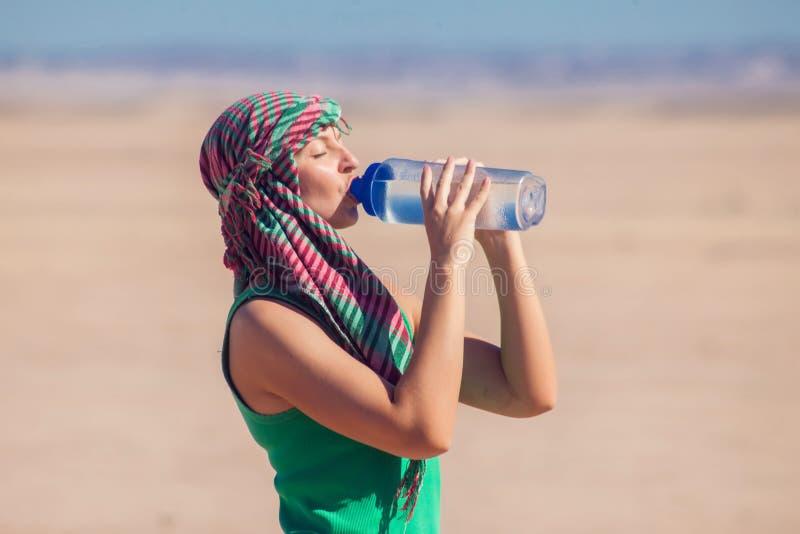 Женщина выпивает воду в пустыне Египта Концепция жаркой погоды стоковые изображения