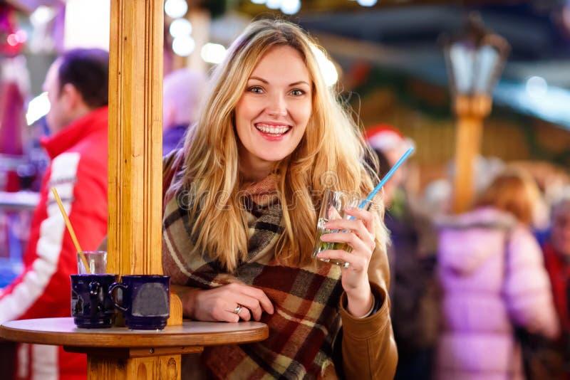 Женщина выпивая горячий пунш на немецкой рождественской ярмарке стоковые фотографии rf