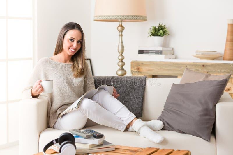 Женщина выпивая и читая кассету на кресле стоковое изображение