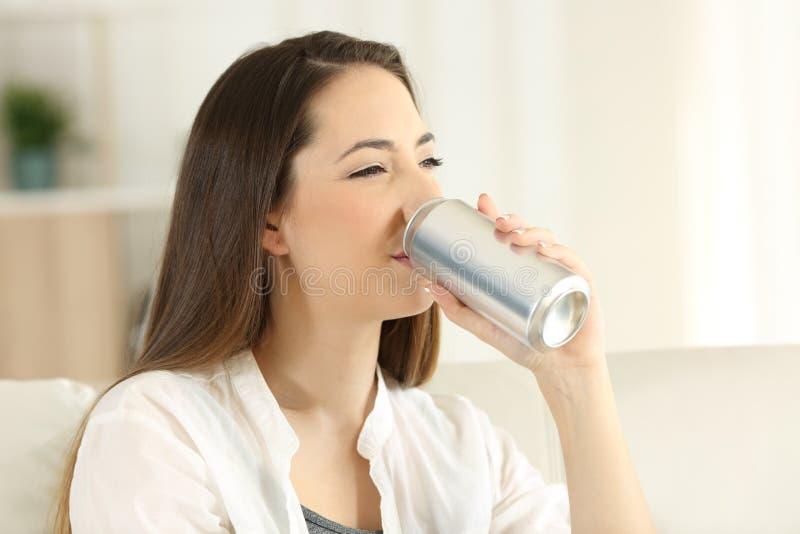 Женщина выпивая освежение соды от чонсервной банкы стоковая фотография