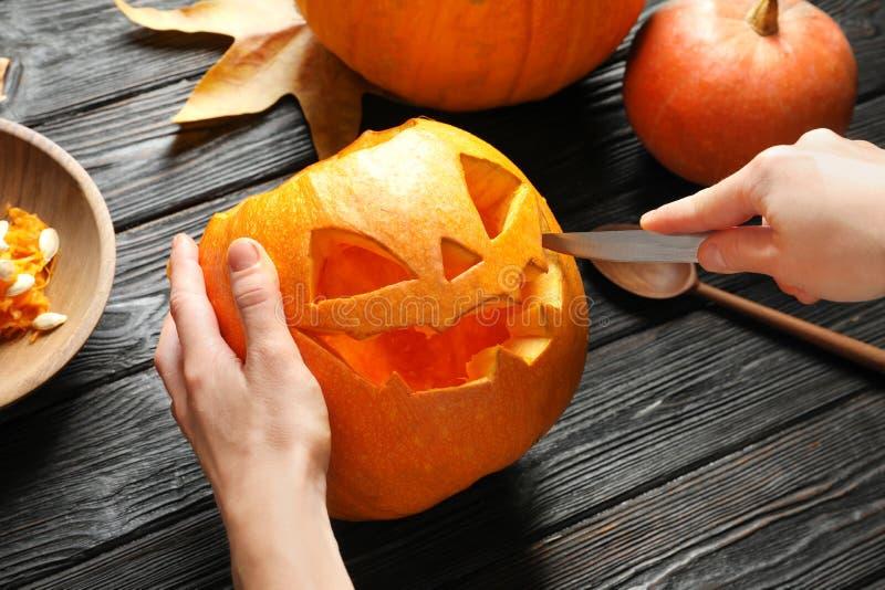 Женщина высекая jack головы тыквы хеллоуина стоковые изображения