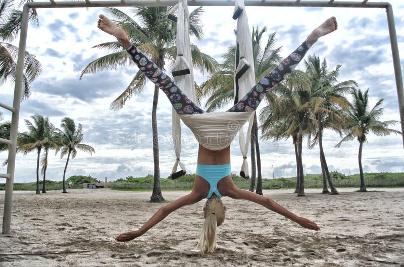 Женщина, выступающая против гравитации йоги стоковое изображение