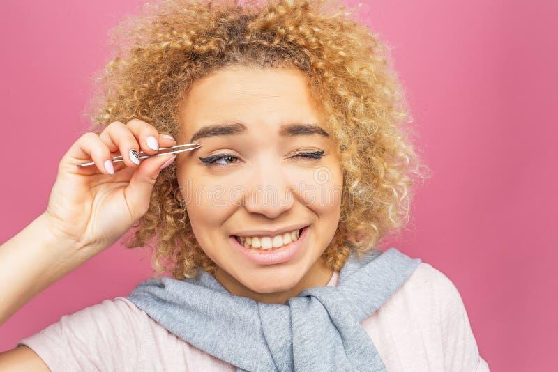 Женщина вытягивает ot волосы от ее чел используя щипчик для того Тягостно Она ` t doesn любит она Изолированный дальше стоковое изображение