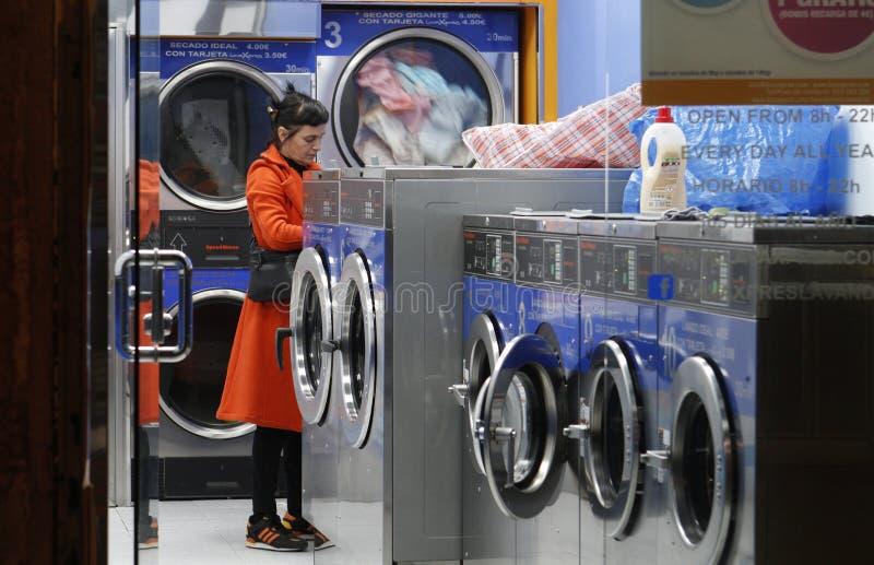 Женщина в автоматической прачечной ждать ее одежды стоковые изображения rf