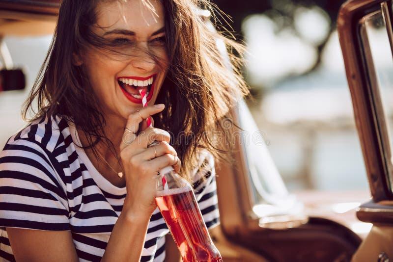 Женщина в автомобиле наслаждаясь выпивающ колу стоковые изображения rf