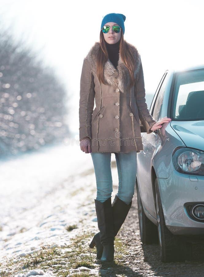 Женщина в автомобиле дороги, пальто овчины меха стоковое изображение rf