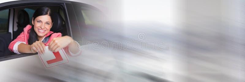 Женщина в автомобиле рвя учащийся l знак с переходом стоковое фото rf