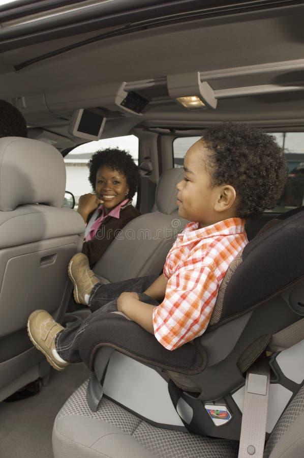 Женщина в автомобиле с малым мальчиком в переднем плане стоковое изображение rf