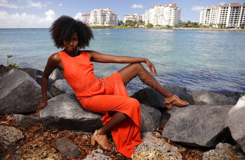 Женщина в апельсине представляя на утесах стоковые фото