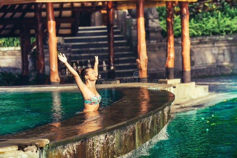 Женщина в бассейне, заплывании и загорать на свете восхода солнца золотом стоковое изображение