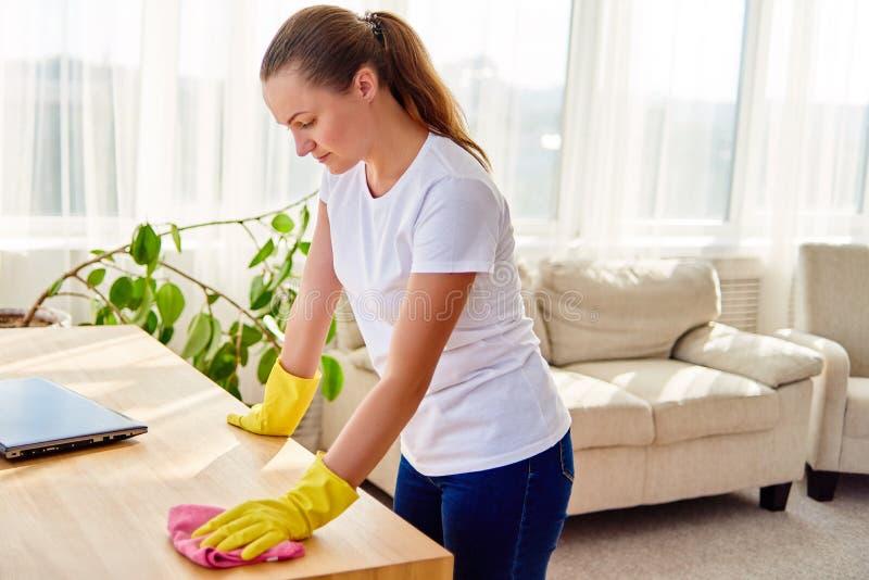 Женщина в белой рубашке и желтых защитных резиновых перчатках очищая дома и обтирая пыль на деревянном tablel с розовой ветошью стоковые фото