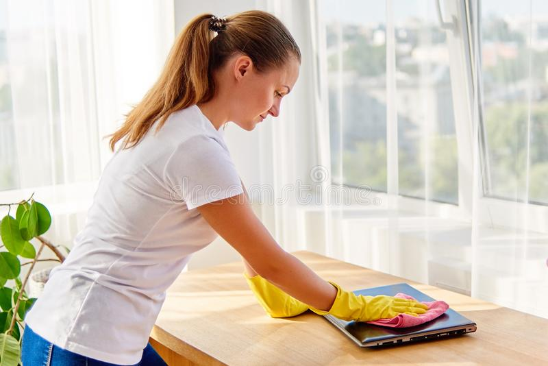 Женщина в белой рубашке и желтых защитных резиновых перчатках очищая дома и обтирая пыль с розовой ветошью на ноутбуке стоковое фото