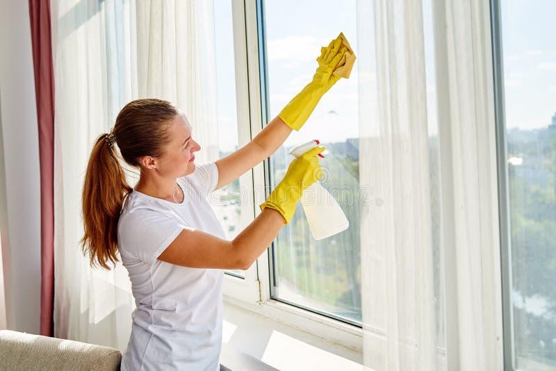 Женщина в белой рубашке и желтых резиновых перчатках очищая окно с брызгами и бульварной газетенкой дома или офисом cleanser, кос стоковая фотография