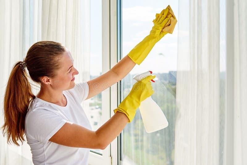 Женщина в белой рубашке и желтых резиновых перчатках очищая окно с брызгами и бульварной газетенкой дома или офисом cleanser, кос стоковые фотографии rf
