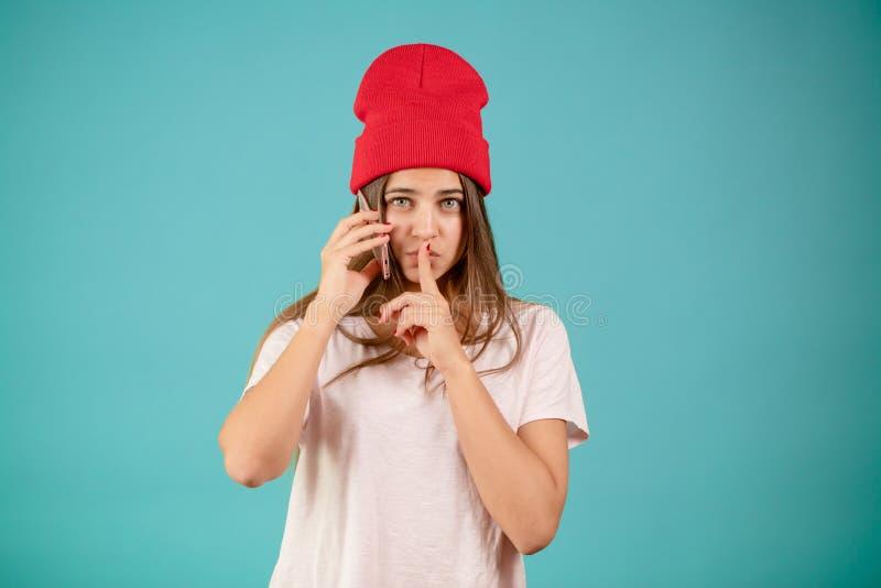 Женщина в белой футболке и красной sporty крышке с положением мобильного телефона стоковое фото rf