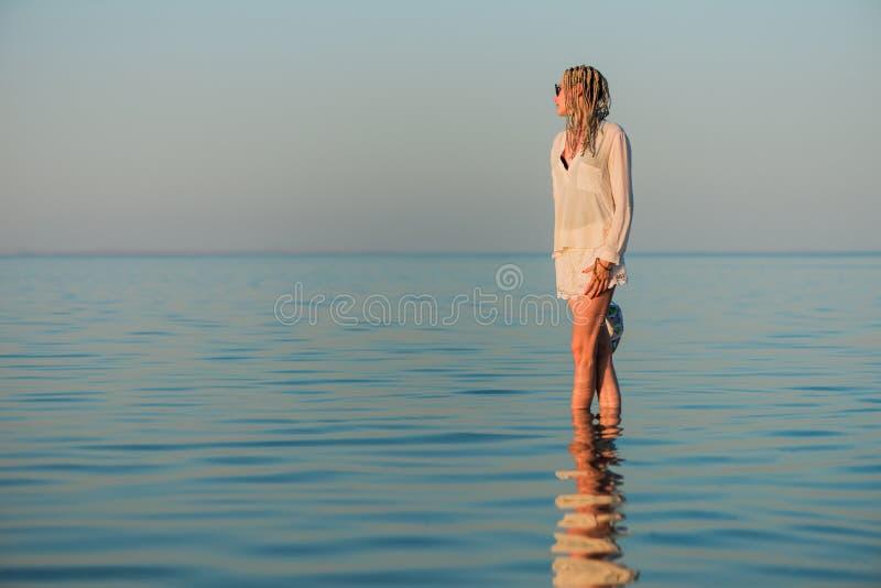 Женщина в белом портрете одежд на море лета стоковое фото