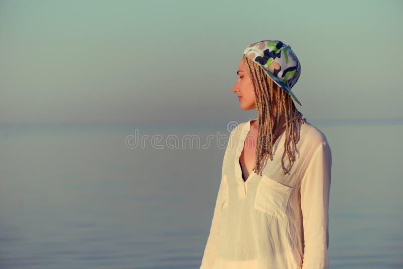 Женщина в белом портрете рубашки и шляпы на море стоковые фото