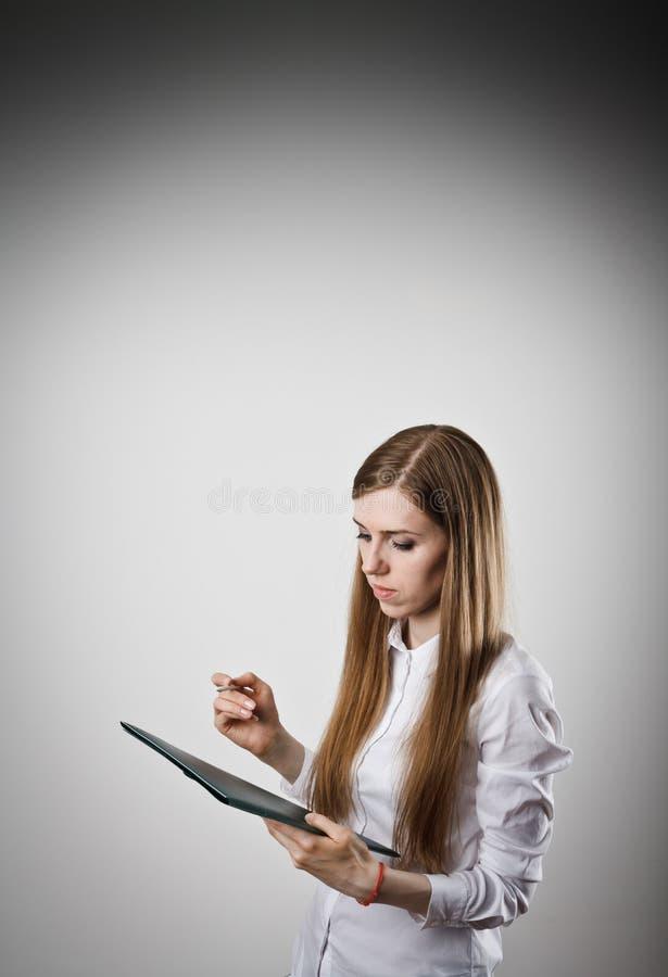 Женщина в белизне держит папку стоковое фото